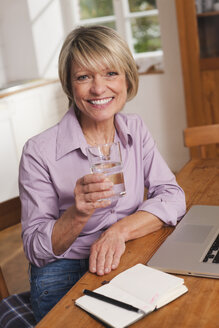 Germany, Kratzeburg, Senior woman with water glass and laptop, smiling, portrait - WESTF016602