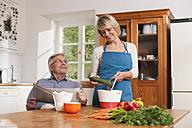 Germany, Kratzeburg, Senior man with newspaper, senior woman preparing food - WESTF016659