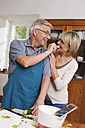 Germany, Kratzeburg, Senior man feeding cucumber slice to senior woman - WESTF016665