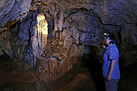 Greece, Crete, Lasithi Plateau, Tzermiado, Woman with head torch at Trapeza cave - SIE001213
