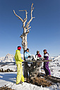 Italy, Trentino-Alto Adige, Alto Adige, Bolzano, Seiser Alm, People resting near bare tree on snowy landscape - MIRF000121