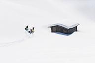 Italy, Trentino-Alto Adige, Alto Adige, Bolzano, Seiser Alm, Group of people near house on ski tour - MIRF000133