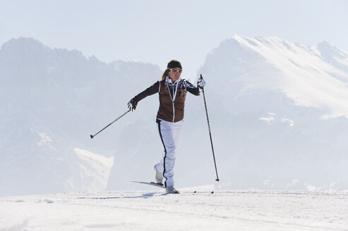 Italy, Trentino-Alto Adige, Alto Adige, Bolzano, Seiser Alm, Mid adult woman doing cross-country skiing - MIRF000160