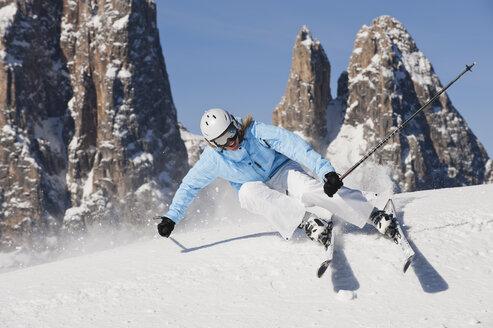 Italy, Trentino-Alto Adige, Alto Adige, Bolzano, Seiser Alm, Young woman skiing near mountain - MIRF000172