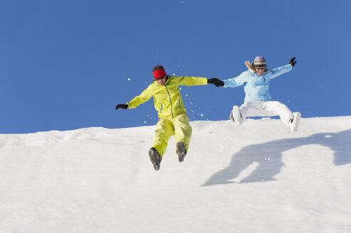 Italy, Trentino-Alto Adige, Alto Adige, Bolzano, Seiser Alm, Man and woman jumping on snow - MIRF000187
