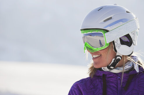 Italy, Trentino-Alto Adige, Alto Adige, Bolzano, Seiser Alm, Young woman wearing skiing helmet and ski goggles, smiling, close up - MIRF000193