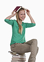 Girl holding book on her head against white background, smiling, portrait - WWF001906