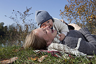 Gemany, Bavaria, Munich, Mother with baby boy lying on grass, laughing - RBF000690
