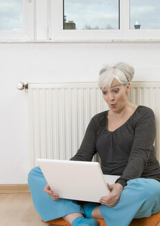 Germany, Duesseldorf, Woman using laptop near heater at home - UKF000216