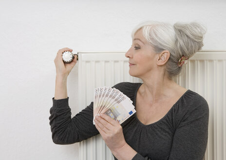 Germany, Duesseldorf, Woman holding banknotes and adjusting heater at home - UKF000200