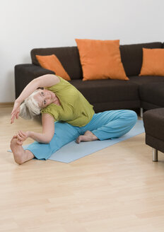 Germany, Duesseldorf, Woman doing yoga near sofa at home - UKF000190