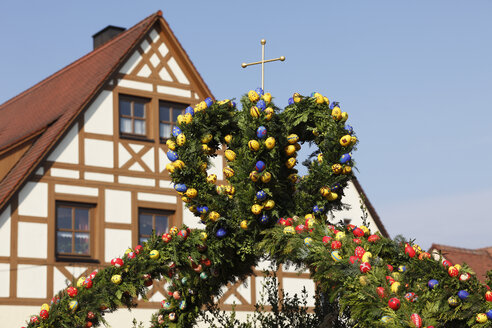 Germany, Bavaria, Franconia, Franconian Switzerland, Kirchehrenbach, View of decorated easter well with timber framed house in background - SIE001402