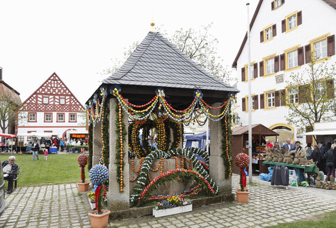 Germany, Bavaria, Franconia, Franconian Switzerland, Hollfeld, View of decorated easter well in easter market - SIE001423