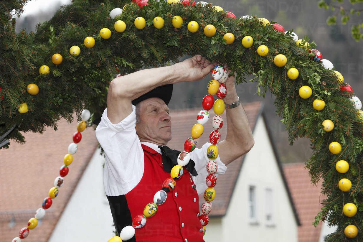 Germany, Bavaria, Franconia, Franconian Switzerland, Muggendorf, Man in traditional costume decorating easter well - SIE001385 - Martin Siepmann/Westend61