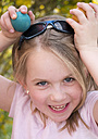 Germany, Bavaria, Close up of girl joking with easter eggs, smiling, portrait - LFF000254