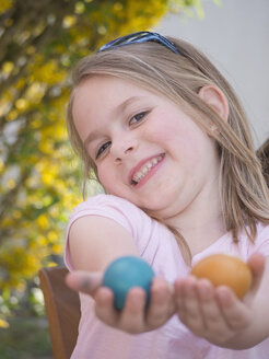 Germany, Bavaria, Close up of girl joking with easter eggs, smiling, portrait - LFF000257