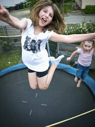 Germany, Bavaria, Two girls jumping on trampoline - LF000260