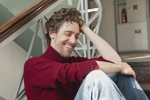 Mid adult man sitting on stairway, smiling - DBF000084