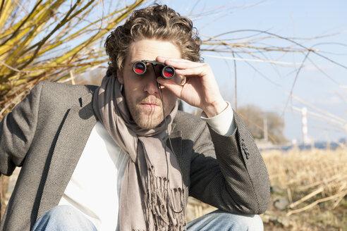 Germany, Hamburg, Man looking through binoculars near Elbe riverside - DBF000124