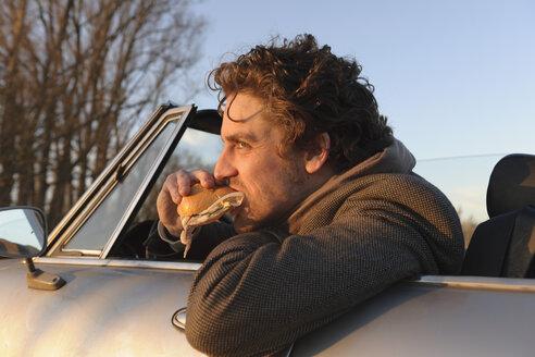 Germany, Hamburg, Man eating fish sandwich in classic cabriolet car - DBF000107