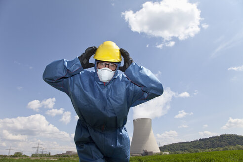Germany, Bavaria, Unterahrain, Man with protective workwear covering his ears in field at AKW Isar - MAEF003285