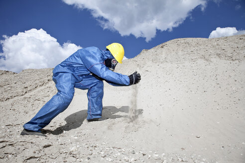 Germany, Bavaria, Man in protective wear spilling sand on sand dune - MAEF003305