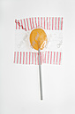 Close up of lollipop in wrapper against white background - TCF001471