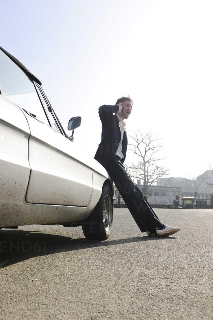 Germany, Hamburg, Mid adult man leaning on vintage car using mobile phone -  DBF000056 - Daniel Butowski/Westend61