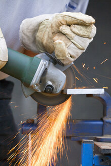 Close up of man cutting piece of iron with angle grinder - TSF000259