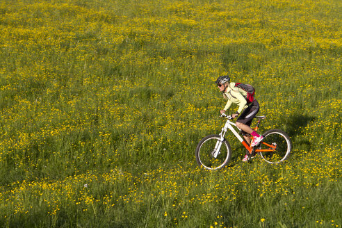 Germany, Bavaria, Schliersee, Woman mountain biking in field - FFF001156