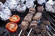 Germany, North Rhine-Westphalia, Düsseldorf, Close up of shashlik spears, tomatoes and onions in aluminium foil on grill - KJF000087
