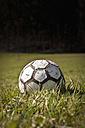 Germany, North Rhine-Westphalia, Düsseldorf, Close up of old football on grass - KJF000086