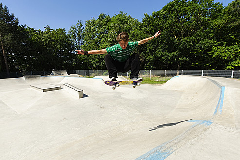 Germany, Duesseldorf, Young man performing tricks with skateboard in skatepark - KJF000105