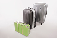 Variety of suitcases and luggages in a row against white background - WESTF016722