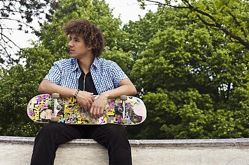 Germany, NRW, Duesseldorf, Man holding skateboard at public skatepark - KJF000112
