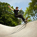 Germany, NRW, Duesseldorf, Man skateboarding at public skatepark - KJF000113