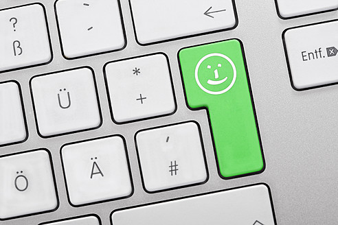Illustration of keyboard having green key with smiley face, close up - TSF000303