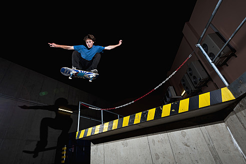 Germany, North Rhine-Westphalia, Duesseldorf, View of young skateboarder performing stunt at night - KJF000118