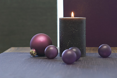 Close up of christmas bauble and candle on table - ASF004358