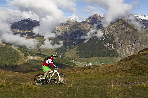 Italy, Livigno, View of woman riding mountain bike - FFF001166