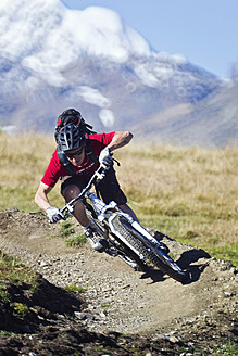 Italy, Livigno, View of man riding mountain bike downhill - FFF001175