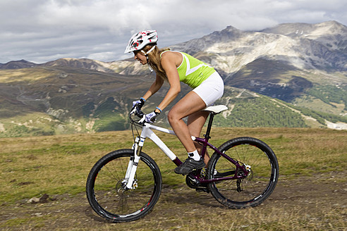 Italy, Livigno, View of woman riding mountain bike - FFF001193