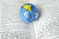 Germany, Close up of earth globe on open dictionary - TCF001538