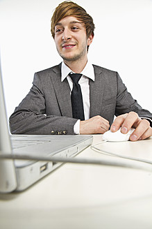 Young businessman working on laptop against white background - MBEF000142