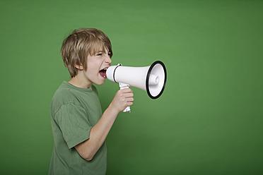 Boy screaming in megaphone against green background - TCF001551