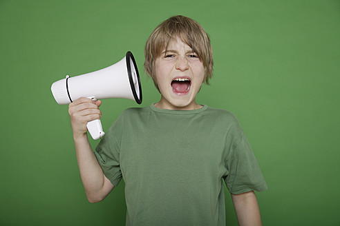 Close up of boy getting irritated by megaphone against green background - TCF001557