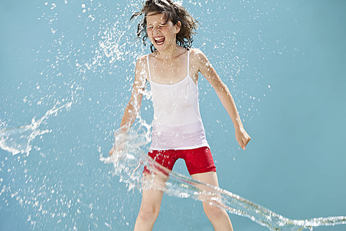 Germany, Girl jumping in splash of water against blue background - MAEF003421