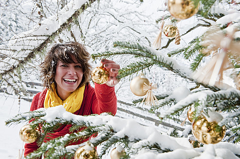 Austria, Salzburg Country, Flachau, Young woman decorating christmas tree in winter - HHF003673
