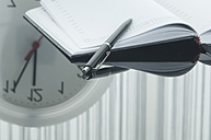 Close up of notebook, pen and clock with reflection on table - ASF004376