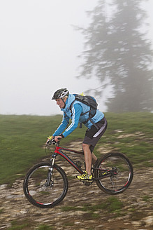 Germany, Bavaria, Chiemgau, Mid adult woman moutainbiking in fog - FFF001200